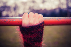 Hand on monkey bar. Closeup on a woman's hand as she is holding onto a monkey bar in the park Stock Image