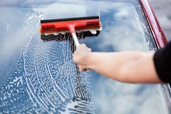 Hand with mop on car. Close-up Of Hand Washing Car Window With Mop stock photos