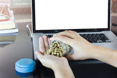 Hand and moringa capsules with blank screen notebook or computer Royalty Free Stock Photos