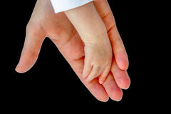 Hand of mother holding arm of baby on black Royalty Free Stock Photos
