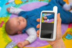 Mother is holding baby monitor camera for safety of her baby. Hand of mother is holding baby monitor camera for safety of her cute baby Royalty Free Stock Images