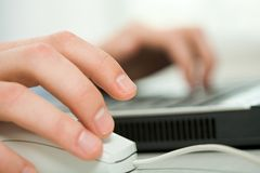 Hand on mouse. Close-up of human hand on white mouse during computer work Royalty Free Stock Image