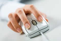 Hand on mouse. Close-up of female hand on white mouse royalty free stock photography