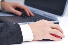 Hand on mouse. Business man at laptop with hand on the mouse in focus, isolated on white Royalty Free Stock Photos