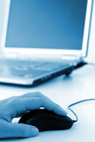 Hand & mouse. Hand on mouse with partial laptop in background in blue tint Stock Photos