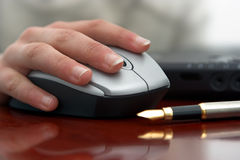 Hand and mouse. Hand holding mouse, on a shiny office table Royalty Free Stock Photos