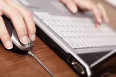 Hand on mouse and laptop keyboard in the back, blured Royalty Free Stock Photo