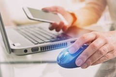 Hand on mouse with smartphone Royalty Free Stock Photos