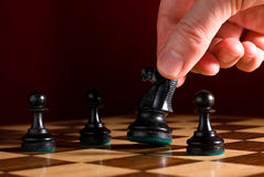 Hand moves knight on chess board. Chess board with pieces as example of game or business concept for power; strategy or success with hand moving knight royalty free stock photo