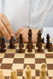 Hand moving chess black piece Royalty Free Stock Images