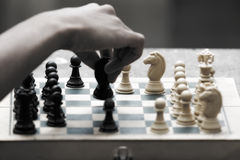 Hand moving chess piece. A hand moving a chess piece on a playing board royalty free stock image