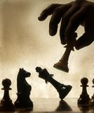Hand moving chess piece Royalty Free Stock Photo