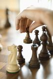 Hand moving chess piece. Caucasian hand moving chess piece royalty free stock photos