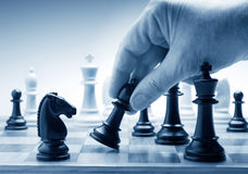 Hand moving a chess piece on board. As a metaphor for various conflicts stock image