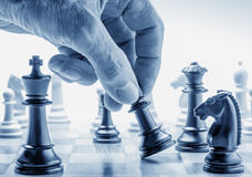 Hand moving a chess piece on board. As a metaphor for various conflicts royalty free stock images