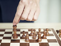 Hand moving a chess piece Stock Photos
