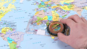 Hand moving a compass over a world map stock footage