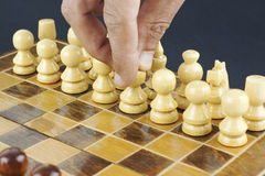 Hand moving a pawn Royalty Free Stock Photography
