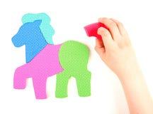 Hand and multicolored foam puzzle Stock Photo