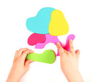 Hand and multicolored foam puzzle Stock Image