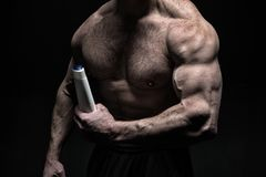 Hand muscular bodybuilder holds plastic bottle. Skin care product. Muscular chest sportsman on black bakground. Product. For body care and skin treatment. Body stock photo