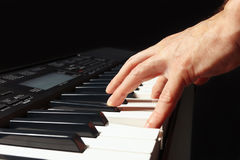 Hand of musician play the keys of the electronic organ on black background Stock Images