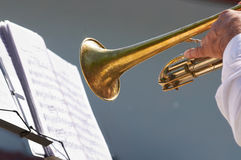 The hand of the musician plays on trumpet. Opposite to a lectern with notes Stock Photo