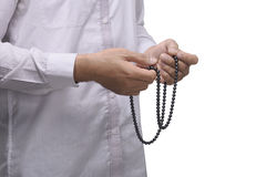 Hand of muslim man with prayer beads pray to god. Isolated over white background Royalty Free Stock Images
