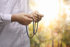 Hand of muslim person pray using prayer beads. With abstract background Stock Images