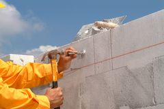 Hand nailing. A worker hand nailing on a concrete wall Royalty Free Stock Images