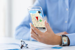 Hand with navigator map on smart phone and watch. Business, technology, navigation, location and people concept - close up of woman hand with gps navigator map royalty free stock photo