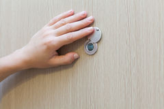 Hand near the door peephole on a new wooden door. Royalty Free Stock Images