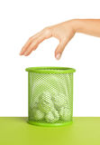 Hand near wastebasket full of waste paper Royalty Free Stock Photography