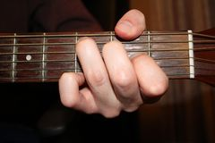 Hand on neck of guitar. Close up of hand grasping neck of guitar Stock Photos