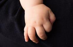 Hand neugeboren auf dunklem Hintergrund Stockfoto