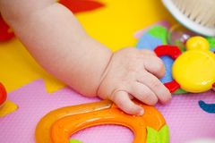 Hand of newborn baby among colorful toys Royalty Free Stock Images