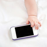 Hand of newborn baby reaches for phone Royalty Free Stock Photography