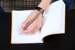 Hand and notebook. Close up Stock Photos