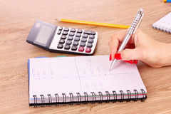 Hand, notepad and calculator on wooden Royalty Free Stock Photo