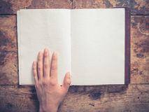 Hand and notepad on a wooden table Royalty Free Stock Image