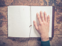 Hand and notepad on a wooden table. A male hand and a big notepad on a wooden table Stock Photo