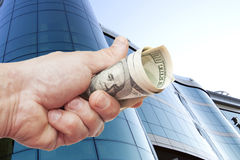 Hand with notes of dollars against office building Stock Photo