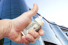 Hand with notes of dollars against office building Royalty Free Stock Photos
