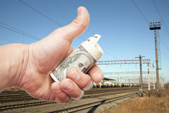 Hand with notes of  dollars against the railroad Royalty Free Stock Photography