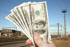 Hand with notes of dollars against the railroad Stock Image