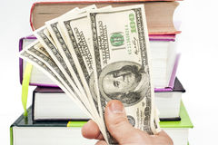 Hand with notes of US dollars against books Royalty Free Stock Photography