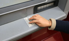 Hand and numeric keypad of the ATM to withdraw money Royalty Free Stock Photos