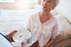 Hand of nurse giving pills to elderly female patient. Senior woman sitting on bed and home care nurse giving medication. Hand of nurse giving pills to elderly Royalty Free Stock Photos