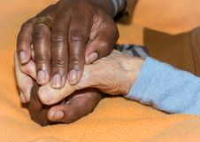 Hand of nurse holding a senior woman. Concept of helping hands, care for the elderly Royalty Free Stock Image