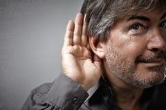 Hand och öra av den lyssnande mannen för tjuvlyssnande royaltyfri bild